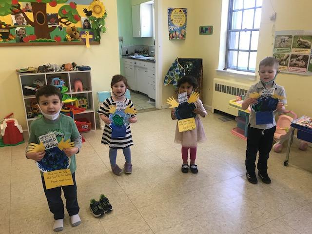 Preschool children hold up art project