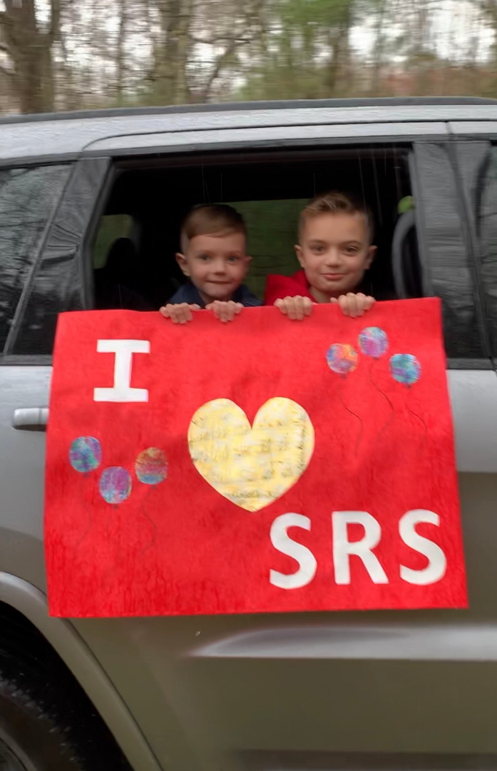 "Students with a sign that reads, ""I (image of a heart) SRS."""