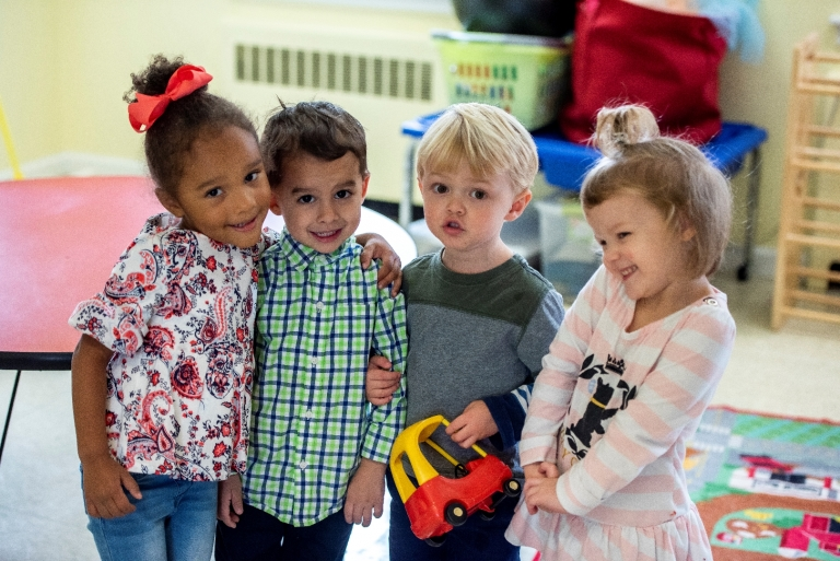 4 preschool students smile together